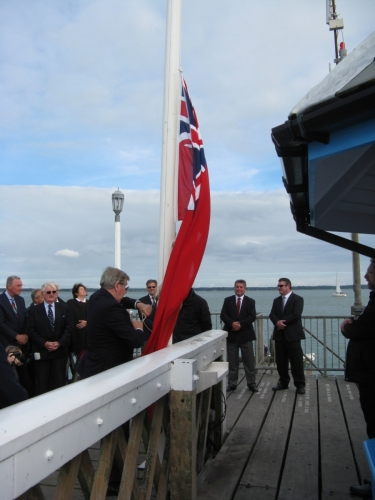 Graham Hall raising Red Ensign at Yarmouth Pier. Merchant Navy Day 3rd September 2015